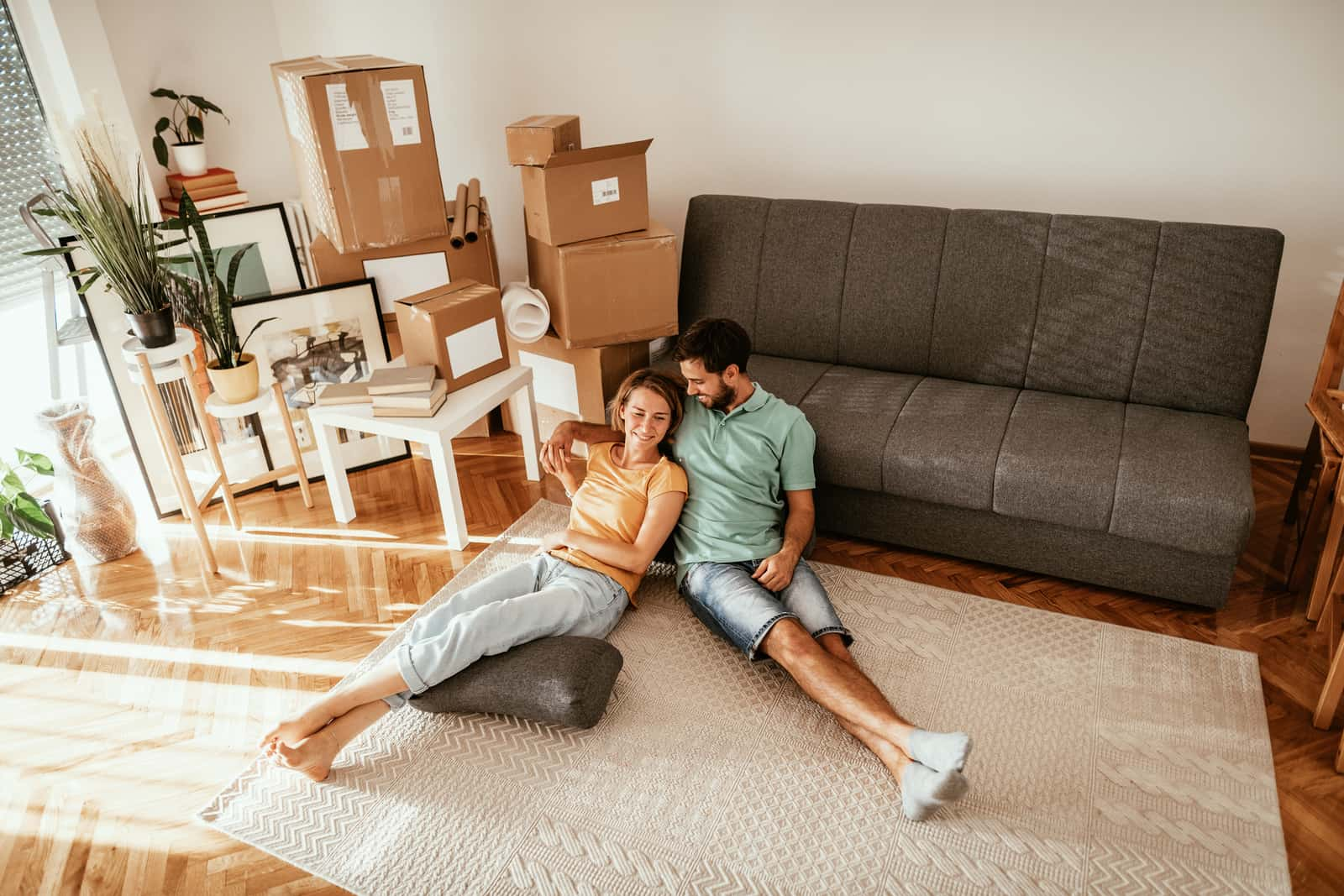 Couple moving in new apartment, lying on carpet and sharing love and happiness after moving in.