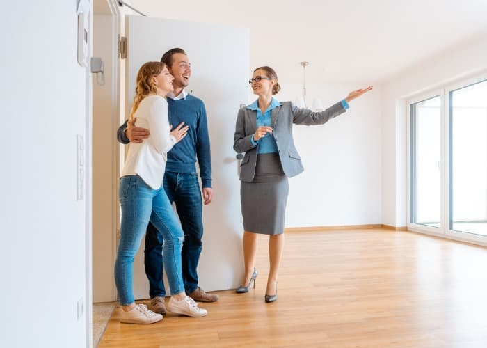real estate agent showing first-time homebuyers house