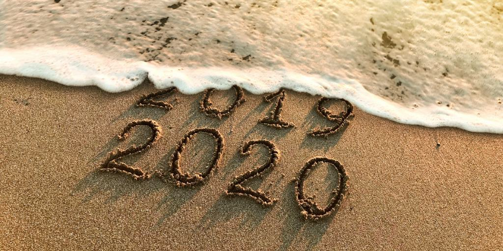 wave washing over 2019 and 2020 in sand