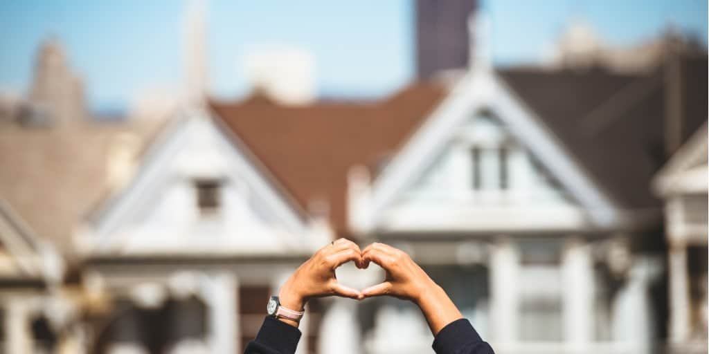 person making heart with hands in front of painted ladies in San Francisco