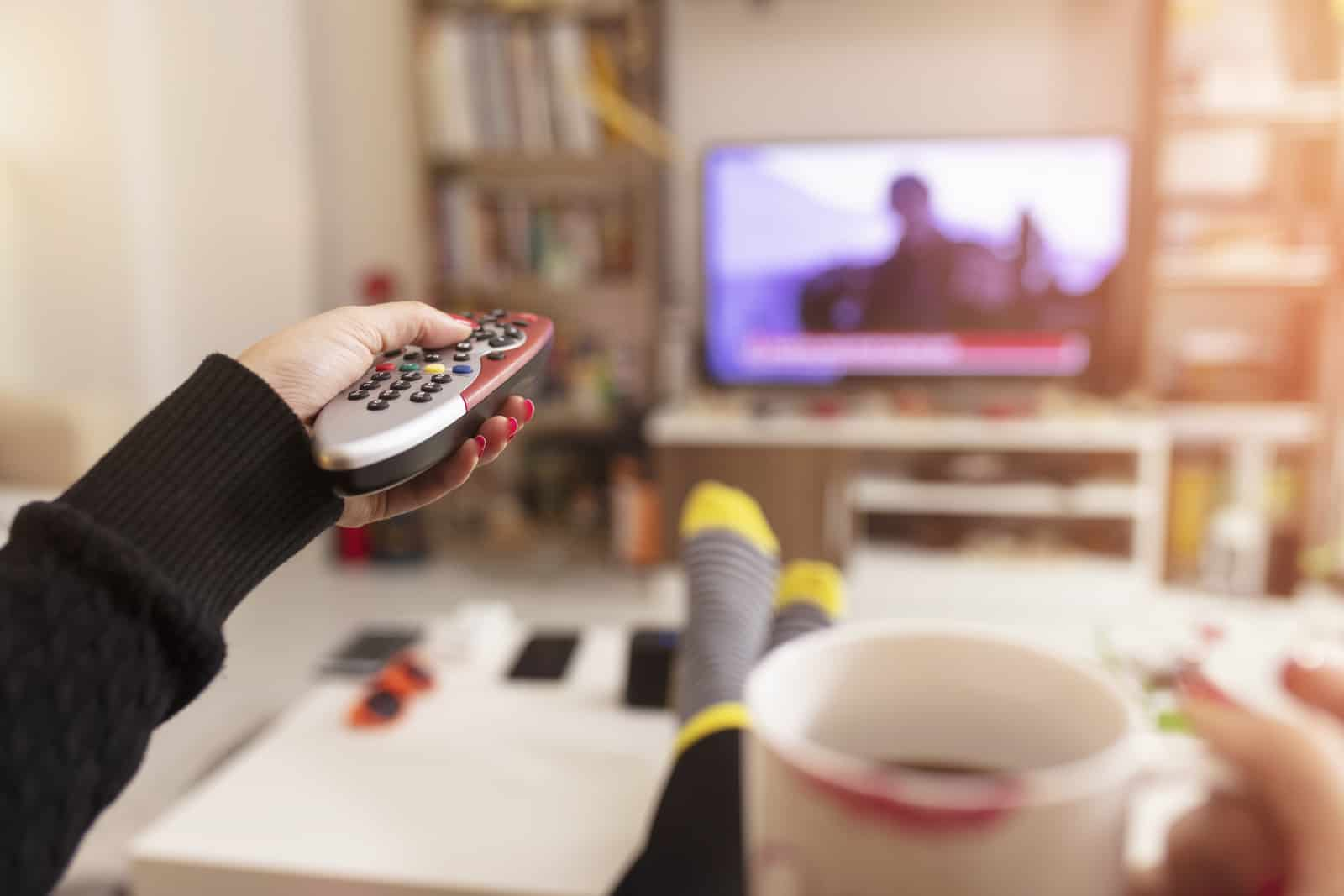woman holding tv remote, watching tv and drinking coffee