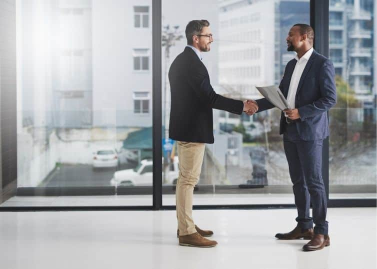 Real estate agent and appraiser shaking hands in a modern building