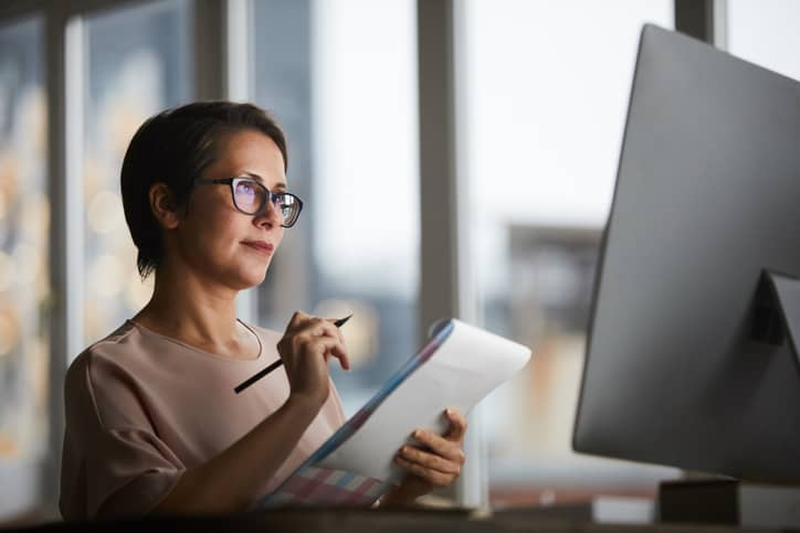 Confident businesswoman with document looking at computer screen and making notes in office