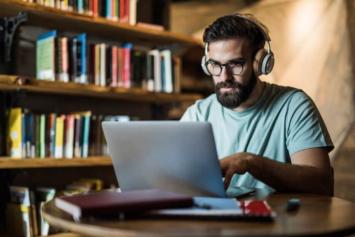 Man studying for national appraisal exam on laptop, wearing headphones in library