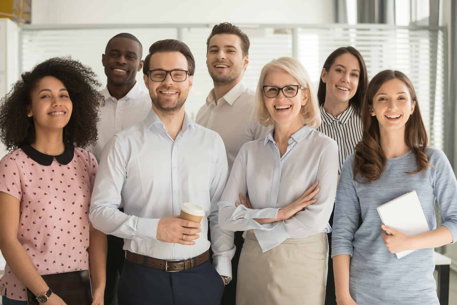 Smiling diverse appraisal team standing looking at camera making team picture in office together