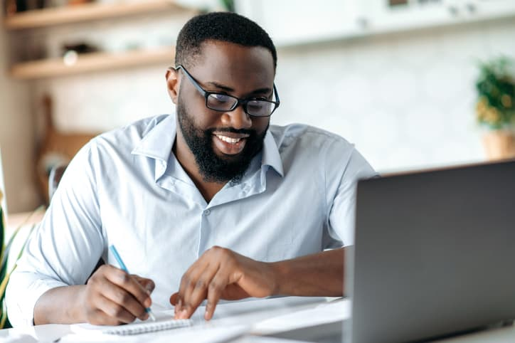 Friendly successful confident african american bearded male with glasses, taking notes, online learning, smiling